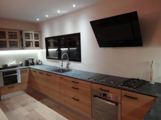 Cuisine avec plan de travail en compact haute densité et façades en chêne